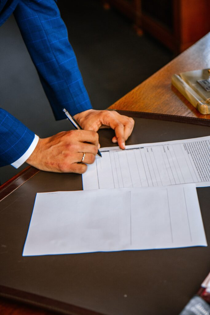 Person in suit writing on paper